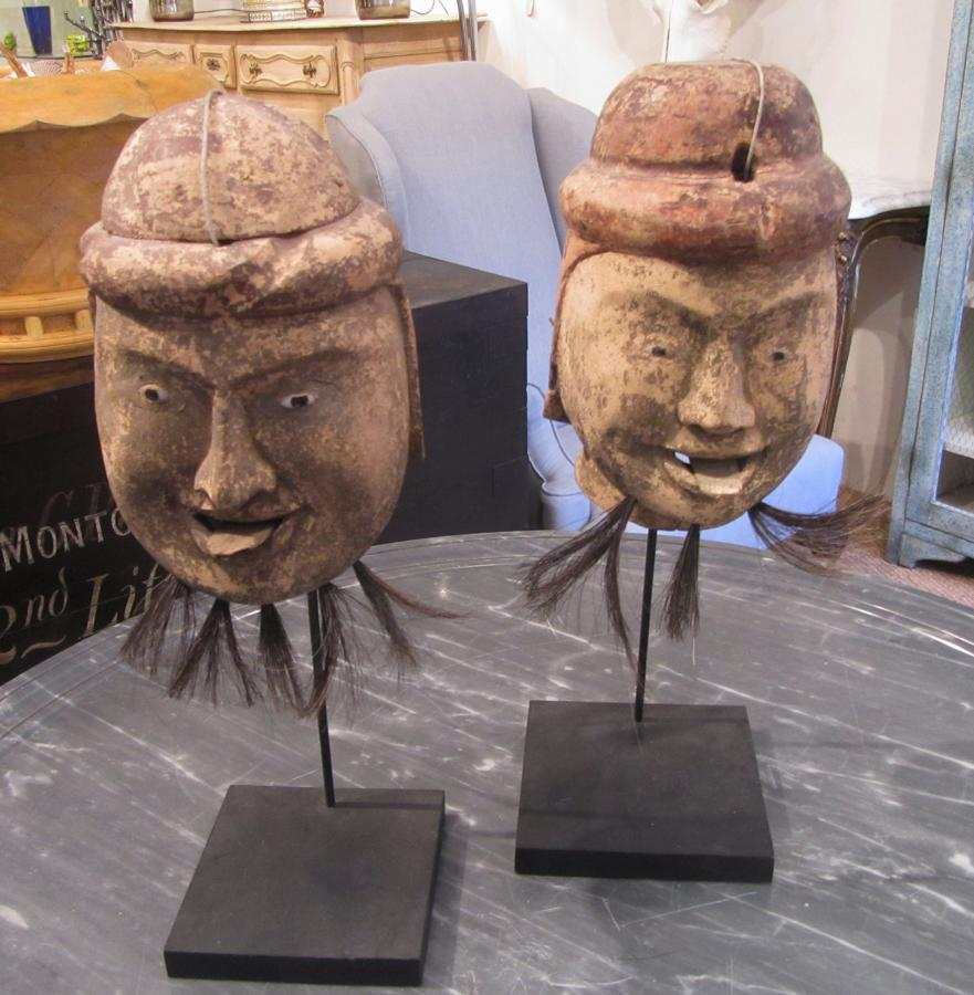 Two carved wood puppet heads