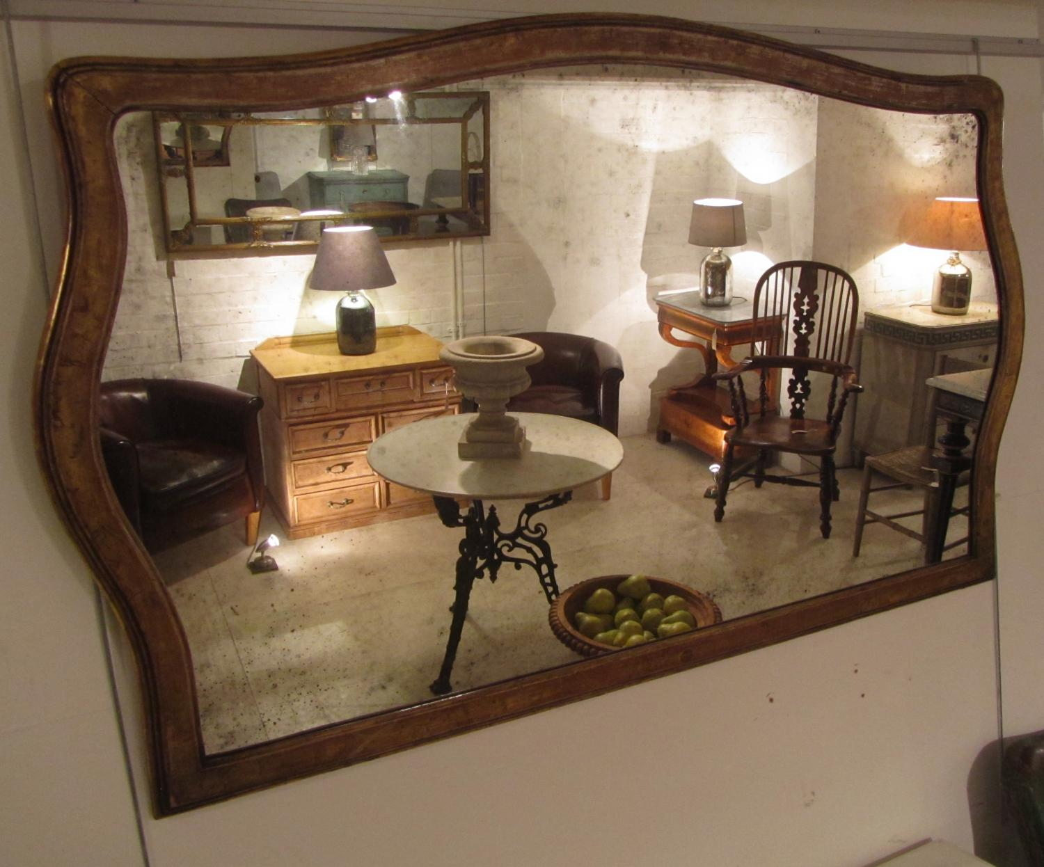 A shaped giltwood overmantle mirror