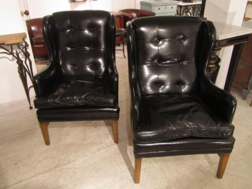 A pair of wing leather armchairs