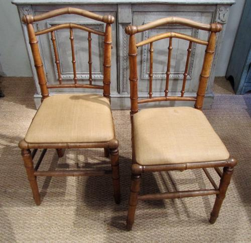 A pair of faux bamboo chairs