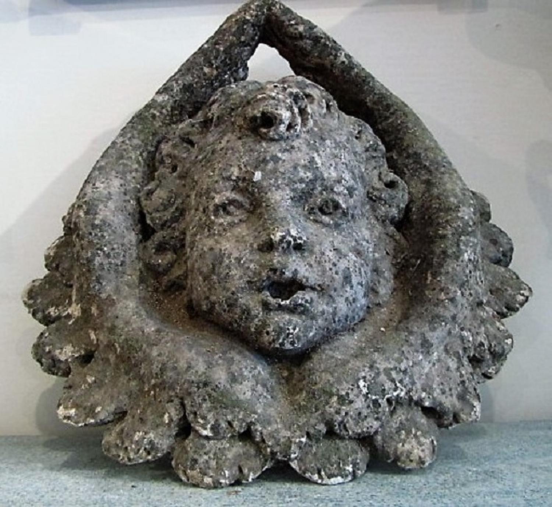 A stone cherub fountain head