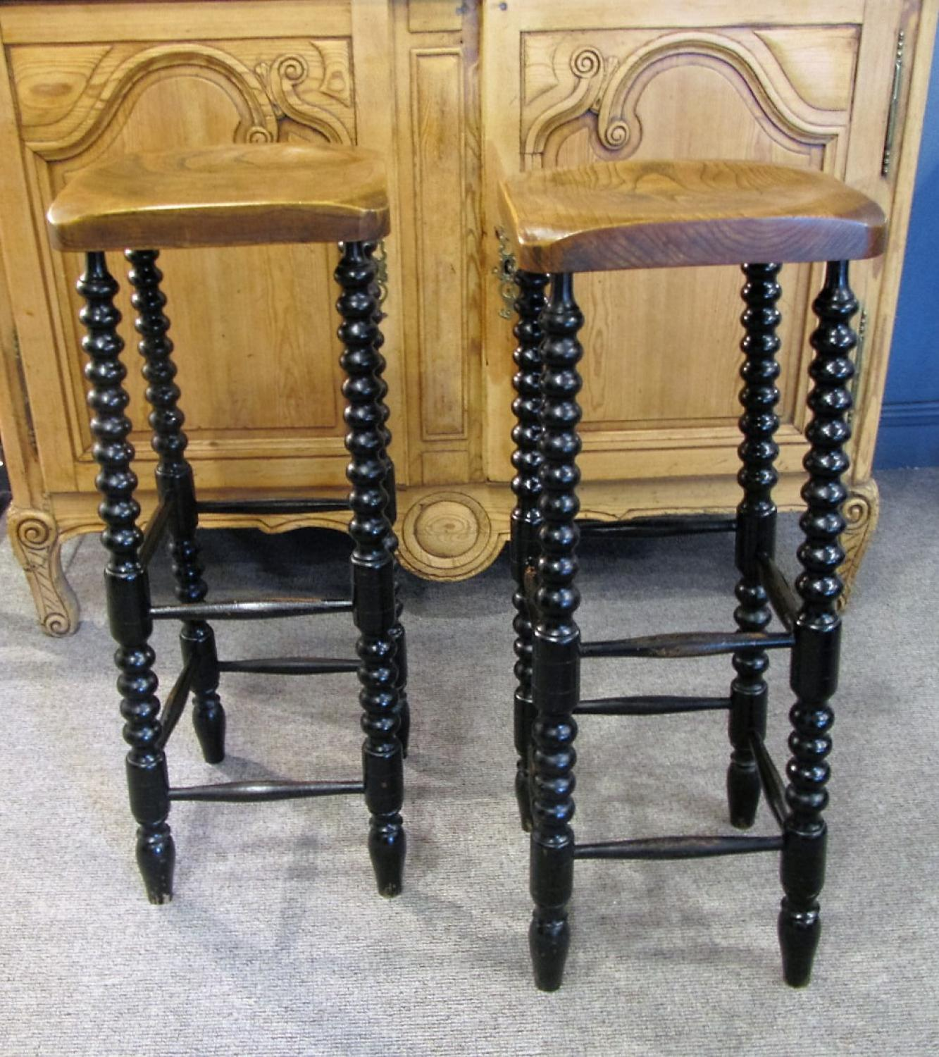 A pair of elm and ebonised counter stools