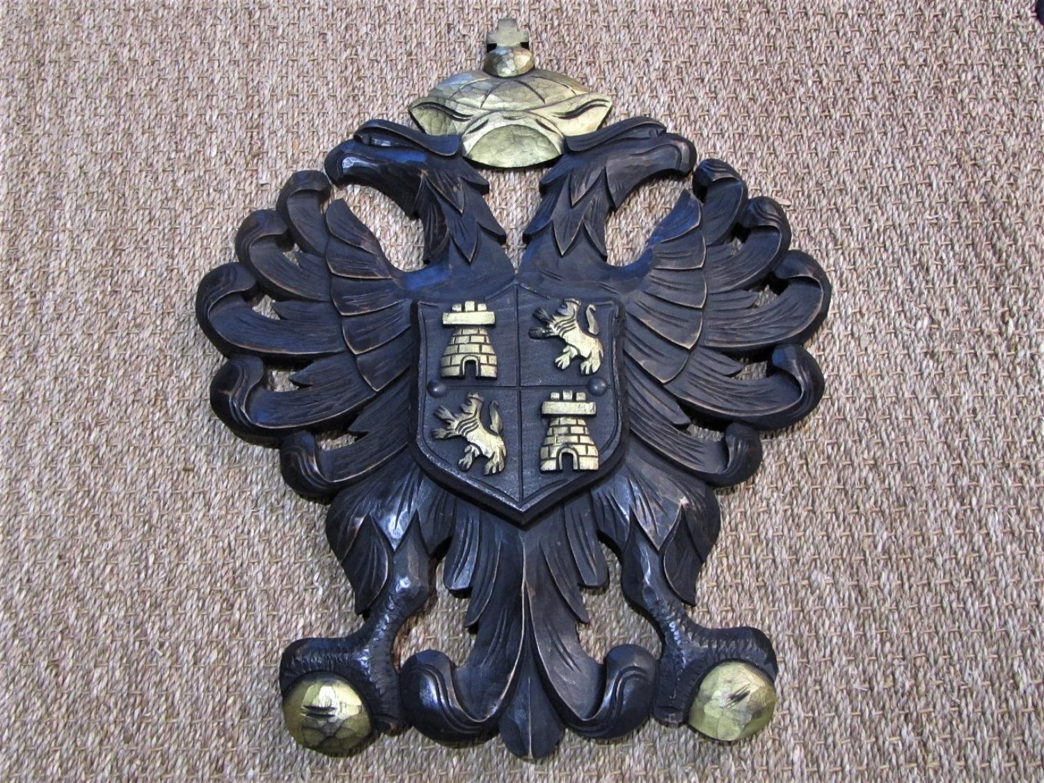 A carved wood armorial coat of arms