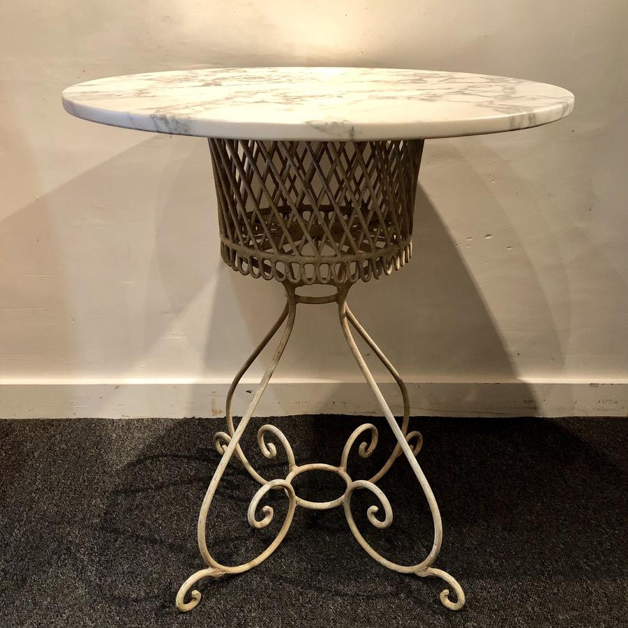 A wrought iron and marble garden table