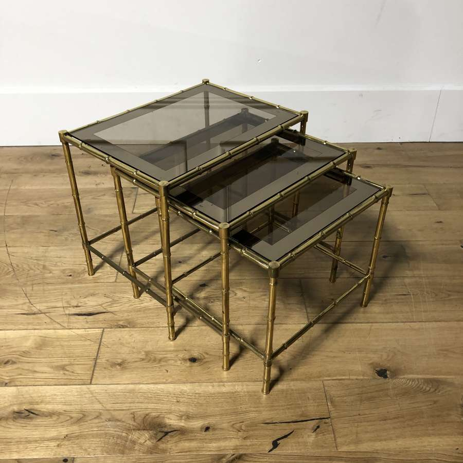 A brass and glass nest of tables