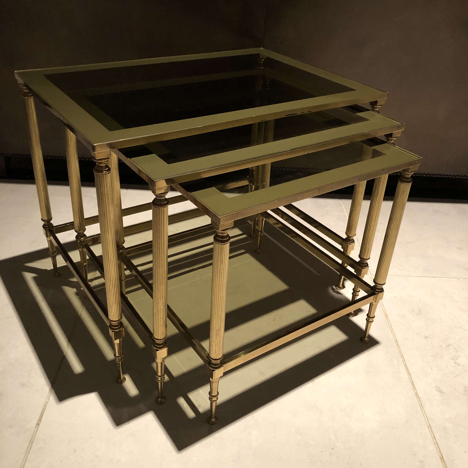 A nest of brass and glass tables