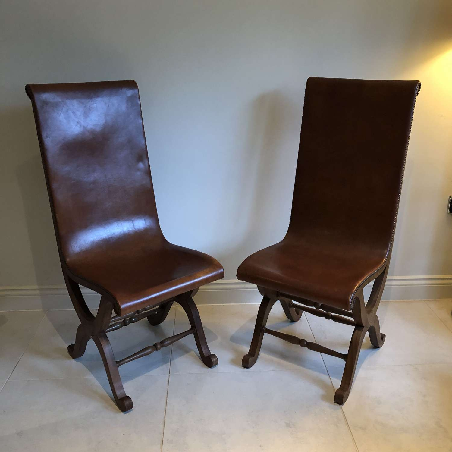 A pair of saddle leather side chairs